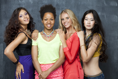 attractive women: Ethnic four women face - isolated on dark wall Stock Photo