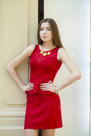 sultry: Sultry portrait of sexy brunette in a red dress on a background of a wall Stock Photo
