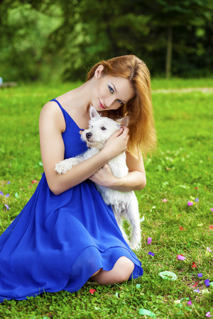 cute dogs: Beautiful young red-hair woman in blue dress, against green of summer park