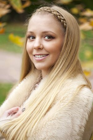 sheepskin: Young beautiful blonde women in a leather sheepskin coat on golden autumn background Stock Photo