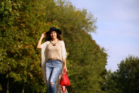 ripped jeans: Young beautiful woman in fashion blue ripped jeans and red bag walking in autumn park Stock Photo