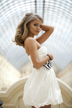 clothing shop: Beautiful young blonde woman in white dress on the background showcases fashion boutique