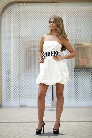vestido blanco: Beautiful young blonde woman in white dress on the background showcases fashion boutique