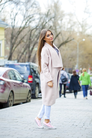 torn jeans: Young beautiful woman in beige coat and torn jeans and pink sneakers on spring street Stock Photo
