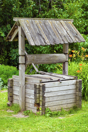 windlass: Old wooden well in summer park Stock Photo