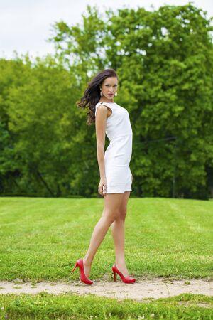 vestido blanco: Mujer joven atractiva en vestido blanco en el parque de verano