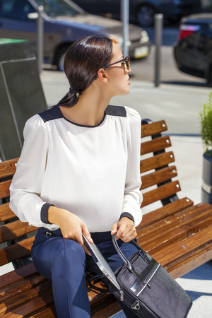 decides: Young beautiful business woman sitting on a bench in the sunny city Stock Photo