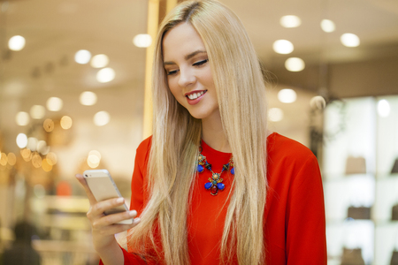 writes: Close up portrait of a beautiful young girl talking on his cell phone in a shopping center