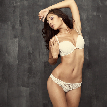 ladies underwear: Portrait of sexy woman in white underwear on a dark wall