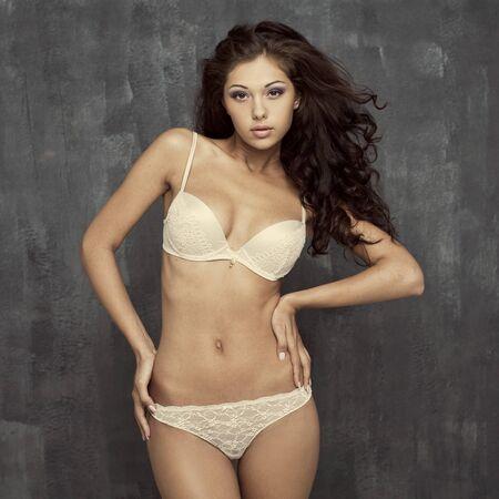 ladies underwear: Portrait of sexy woman in white underwear on a dark wall