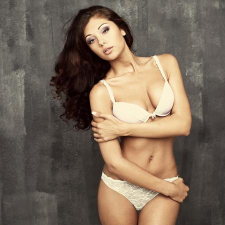 femme en sous vetements: Portrait d'une femme sexy en lingerie blanche sur un mur sombre