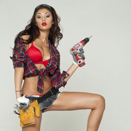Young sexy woman holding a construction drill Stock Photo