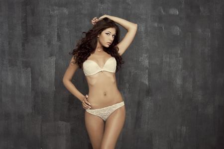 young woman in underwear: Portrait of sexy woman in white underwear on a dark wall