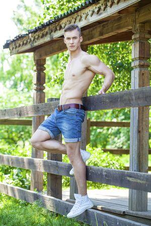 cuerpos desnudos: Retrato atractivo de un modelo masculino descamisado muy muscular en la sombra en el fondo de las paredes de madera viejas