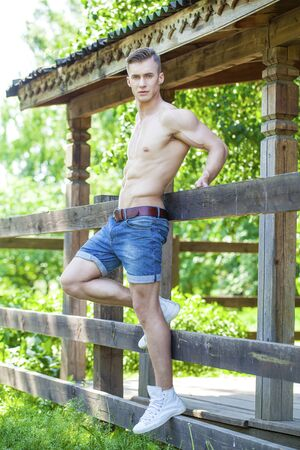 Sexy portrait of a very muscular shirtless male model in the shadow on the background of the old wooden walls