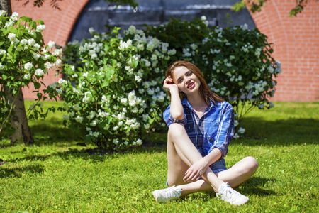 brown haired: Young beautiful brown haired woman in blue shirt and jeans short sitting on green grass Stock Photo