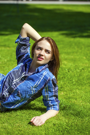 lies down: Young beautiful brown haired woman in blue shirt lying on green grass