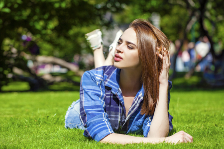 Young beautiful brown haired woman in blue shirt and jeans short lying on green grass Stock Photo