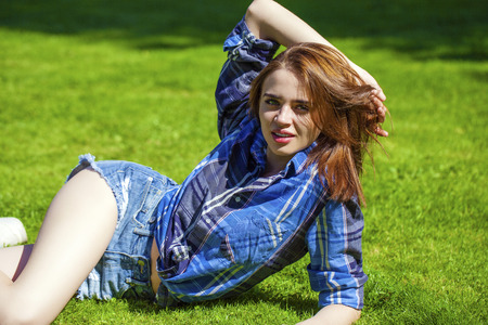 lies down: Young beautiful brown haired woman in blue shirt and jeans short lying on green grass Stock Photo