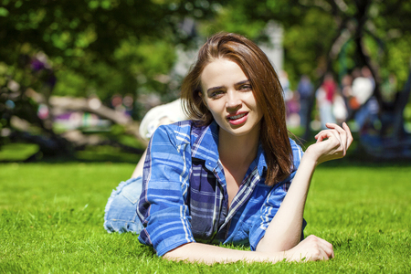 brown haired: Young beautiful brown haired woman in blue shirt and jeans short lying on green grass Stock Photo