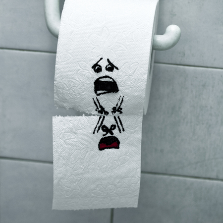 A roll of toilet paper and felt tip pen drawn funny faces Stok Fotoğraf