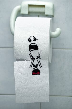 A roll of toilet paper and felt tip pen drawn funny faces Stock Photo