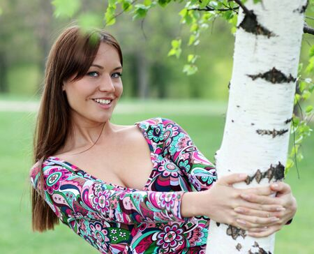 Portrait of the young beautiful woman on a background of leaves of a birch photo