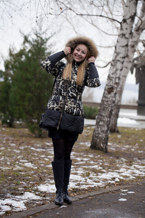 brown haired: Portrait in full growth of a beautiful young brown haired woman on the background of a winter park