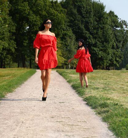 red dress: Beautiful woman in red dress walking summer street