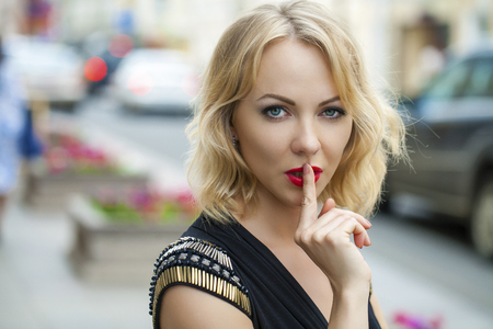 quietly: Young beautiful blonde woman has put forefinger to lips as sign of silence, outdoors