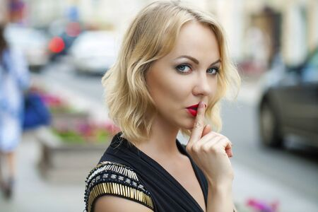 forefinger: Young beautiful blonde woman has put forefinger to lips as sign of silence, outdoors
