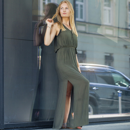wall mirror: Portrait in full growth, Young beautiful blonde woman in long green dress posing against a background of a wall mirror