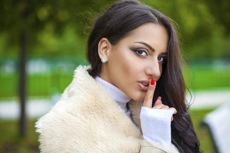 silencio: Retrato de niña árabe atractiva con el dedo en los labios, el concepto de estudiante muestra tranquilo, silencio, gesto secreto, joven mujer bonita morena en el otoño de parque