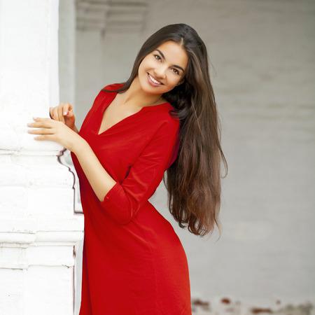 Closeup ritratto di giovane donna bella in abito rosso
