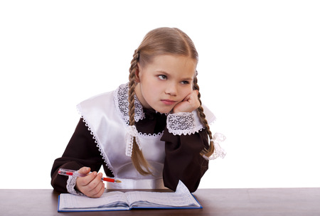 schoolgirl in uniform: Sad schoolgirl sits at a school desk, isolated on a white background Stock Photo