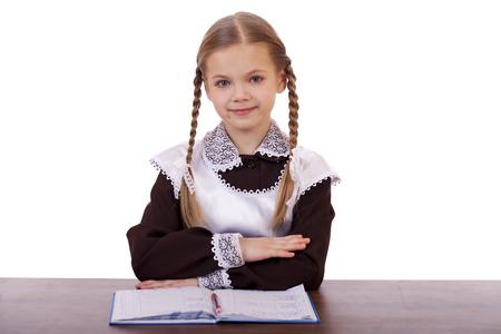 colegiala: Colegiala hermosa joven que se sienta en un escritorio, aislado en un fondo blanco