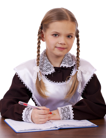 schoolgirl in uniform: Young beautiful schoolgirl sitting at a desk, isolated on a white background