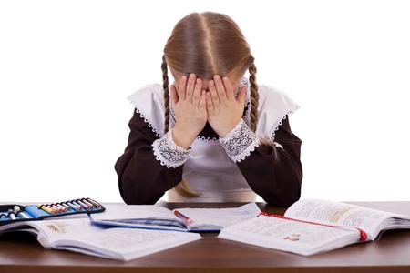 colegiala: Colegiala triste se sienta en un escritorio de la escuela, aislado en un fondo blanco Foto de archivo