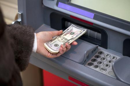 automatic transaction machine: Mujer mano mostrando billetes de d�lar frente a la atm roja