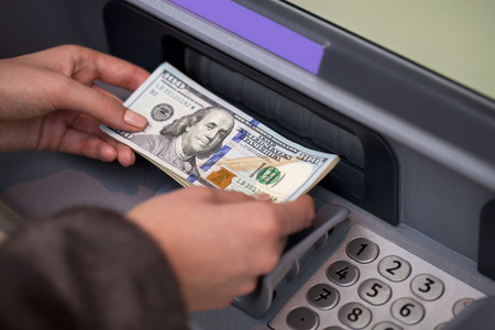 Woman hand showing dollar banknotes in front of the red atm Standard-Bild
