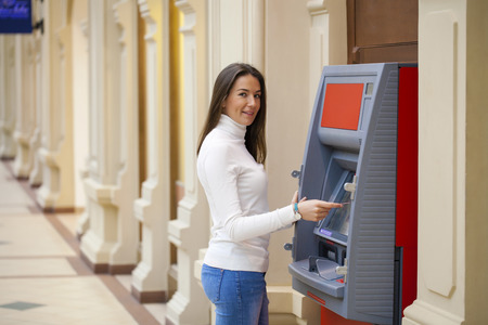 Young happy brunette woman withdrawing money from credit card at ATM Stock Photo