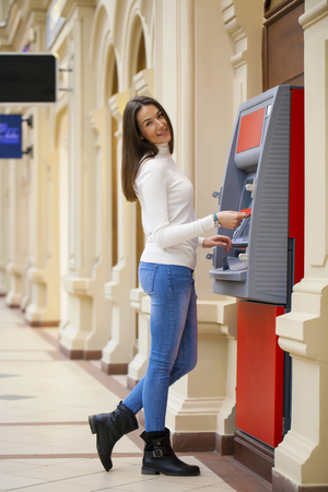 withdrawing: Young happy brunette woman withdrawing money from credit card at ATM Stock Photo