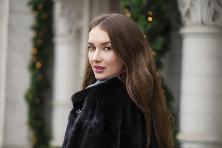 visone: Giovane donna bella in elegante cappotto di visone su uno sfondo di una strada d'inverno