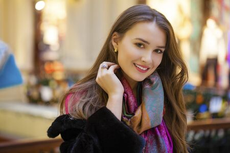 urban people: Young beautiful woman in a black mink coat posing on the background of shop windows