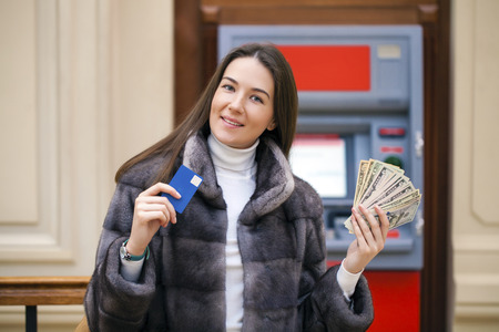 Woman hand showing dollar banknotes in front of the red atm Stock Photo