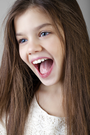 boca abierta: Retrato de una morena encantadora niña, aislada en el fondo gris Foto de archivo