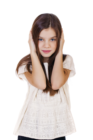 hands covering ears: Portrait of a charming little girl covering ears with hands, isolated on white background Stock Photo