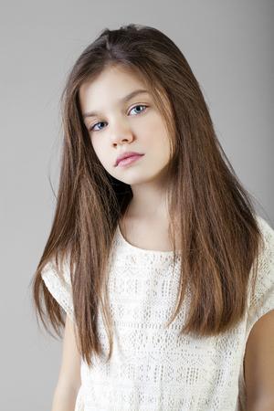 petite fille avec robe: Portrait d'une brunette charmante petite fille, isolé sur fond gris Banque d'images