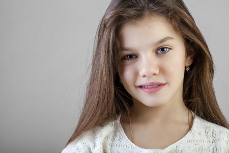 Portret van een charmant donkerbruin meisje, dat op grijze achtergrond wordt geïsoleerd