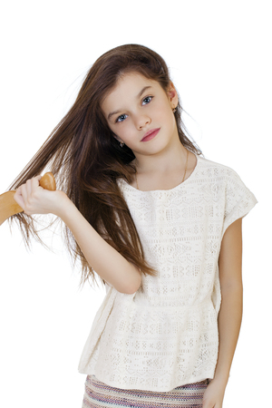 unruly: Hair care concept with portrait of little brunette girl brushing her unruly, tangled long hair isolated on white